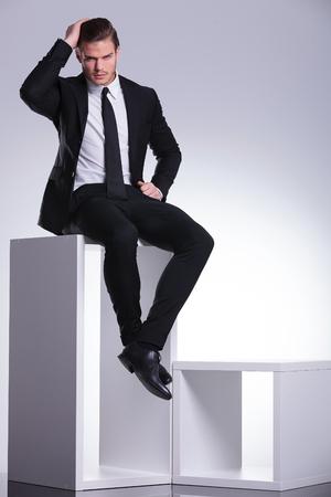 hombre sentado: Joven elegante hombre de negocios sentado en un mueble moderno de color blanco, mientras que la fijación de su cabello.