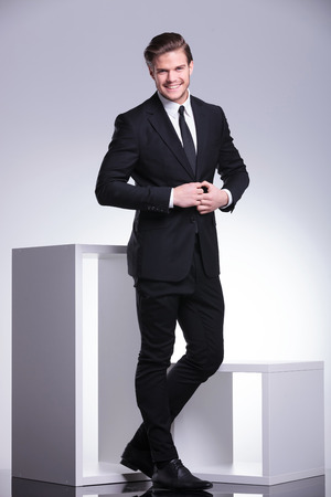 full suit: Full body picture of an attractive business man closing his jacket while smiling for the camera.  Stock Photo