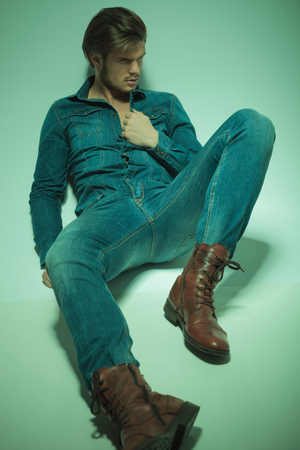 young man jeans: Attractive young fashion man looking away from the camera while lying on the floor pulling his shirt.