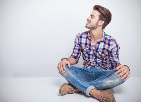 hombre sentado: Enfriar joven sentado una mesa blanca con las piernas crosed mirando de lejos mientras sonriendo. Foto de archivo