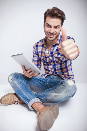 Handsome young fashion man sitting on the floor showing thumbs up gesture while holding a tablet pad computer. photo