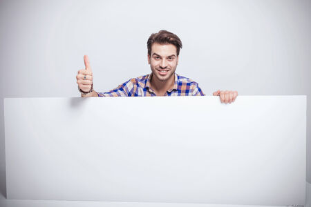 Smiling young handsome man showing the thumbs up gesture while holding a empty white pane. photo