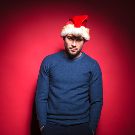 Sexy young man wearing a red santa hat holding his hands in pockets. Leaning on red background. photo
