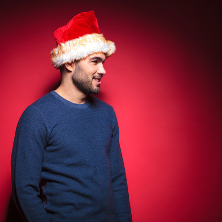 Side view of a man wearing a santa hat, smiling and looking away from the camera. Against red background. photo