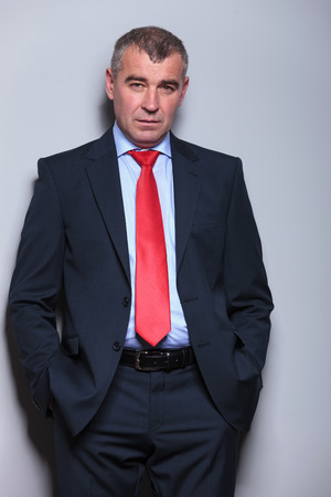 Picture of a serious middle aged business man looking at the camera while holding his hands in pocket, against a grey wall.