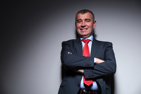 business for the middle: Picture of a middle aged business man smiling for the camera while holding his arms crossed. Stock Photo
