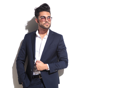 hand in pocket: Cool business man wearing sunglasses, pulling his jacket while leaning on a white wall with one hand in his pocket Stock Photo