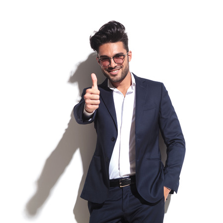 Handsome business man leaning on a white wall while showing thumbs up holding one hand in his pocket. photo