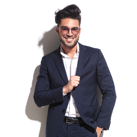 pulling hair: Attractive business man wearing sunglasses, smiling and pulling his jacket while leaning on a white wall.