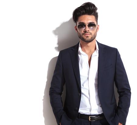 beau jeune homme: Gros plan d'un homme d'affaires beau tenant ses mains dans la poche tout en s'appuyant sur un mur blanc, en regardant la cam�ra Banque d'images