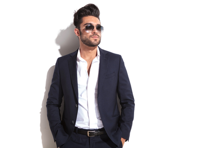 latin man: Cool business man holding his hands in pocket, leaning on a white wall while looking away from the camera Stock Photo