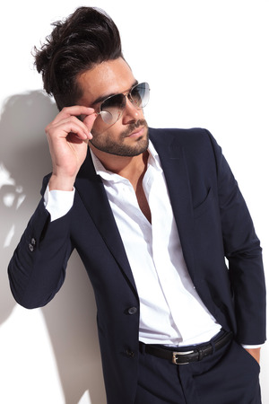 angle view of a handsome business man putting on his sunglasses with one hand in his pocket, looking away from the camera photo