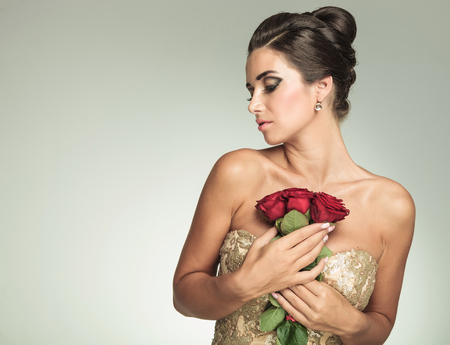 elegant woman in dress holding red roses to her chest and looks to side, in studio photo