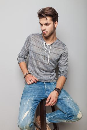 Hombre de la manera que mira abajo mientras está sentado en un taburete, en el fondo gris.