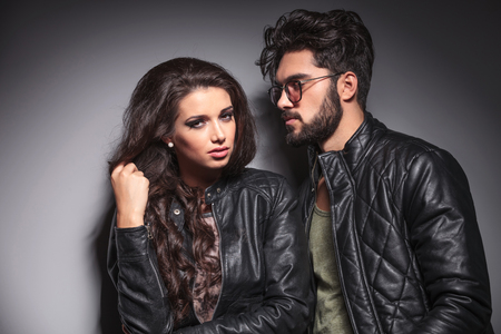 leather jacket: Young fashion woman pulling her hair while her lover is looking at her. Against a grey wall. Stock Photo