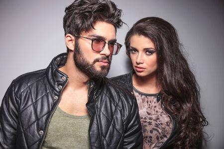 poses de modelos: Pareja de moda joven posando, el hombre est� mirando a otro lado mientras que la mujer est� mirando a la c�mara. Foto de archivo