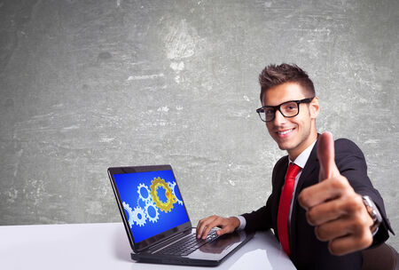 side view of a satisfied business man working on laptop and making the ok gesture photo