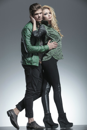 man woman hugging: Full body picture of a beautiful fashion woman holding her lover while he is holding her. Both looking at the camera.