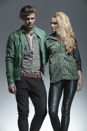 Fashion man and woman holding each other, the woman is looking away while the man is looking at the camera. Imagens