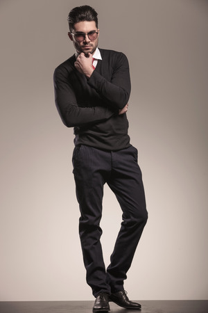 black sweater: Attractive business man fixing his beard while looking at the camera, full body image.