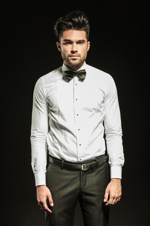 hair bow: Young business man wearing a white shirt with and a bowtie posing for the camera.