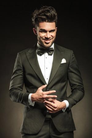 그의 반지를 담합하는 동안 카메라에 웃 고 행복 우아한 사업 사람.