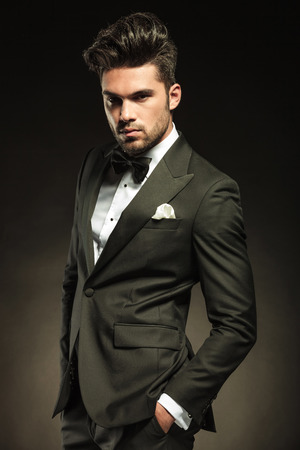 Элегантный деловой человек, глядя на Cameta удерживая руки в кармане. На черном студии Справочный. Фото со стока