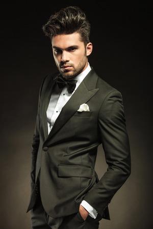 hombres jovenes: Hombre de negocios elegante mirando el Cameta mientras mantiene sus manos en el bolsillo. El fondo de color negro del estudio.