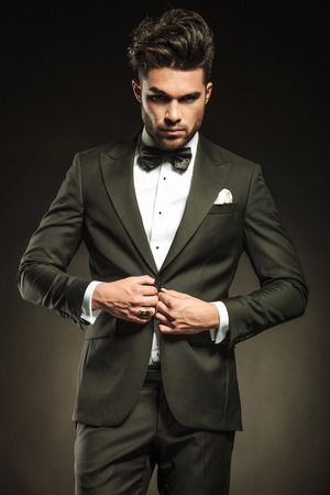 Young elegant business man looking at the camera while arranging his tuxedo.