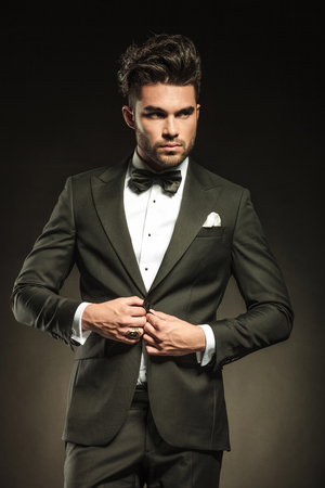 white suit: Elegant business man arranging his tuxedo while looking away from the camera.