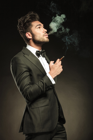 cigarette smoke: Side view of a young business man blowing smoke while holding a cigarette in his right hand. Looking up, on black studio background. Stock Photo