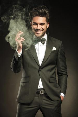 man smoking: Feliz el hombre de negocios sonriendo para la c�mara mientras sostiene un cigarrillo humeante en la mano derecha.