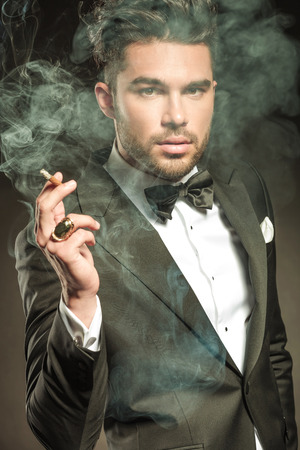 Close up picture of a handsome business man blowing smoke while holding a cigarette in his hand.