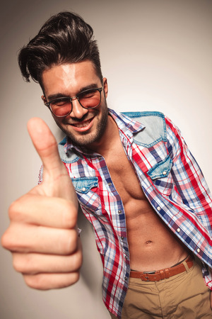 Young fashion man wearing sunglasses showing the thumbs up gesture.