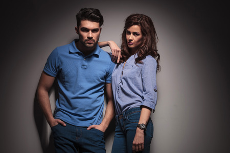 Beautiful fashion woman leaning on her boyfriend, the man is holding his hands in pocket. photo
