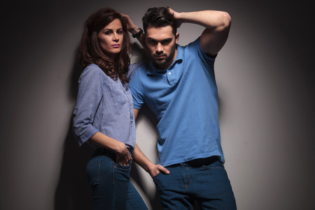 Hot fashion couple posing together, both fix their hair while looking at the camera. photo