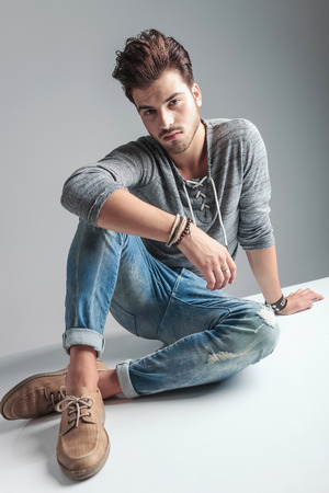 body image: Full body image of a young fashion man relaxing on grey studio backgroud, while looking at the camera.