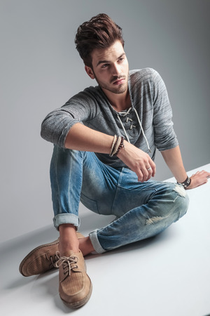 casual fashion: Angle view of a young casual fashion man sitting on the floor while looking away from the camera. Stock Photo