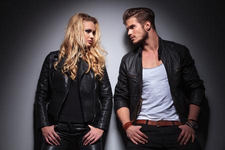Hot fashion paar leunend op een grijze muur, terwijl op zoek naar elkaar, zowel hun duimen in de pockts.