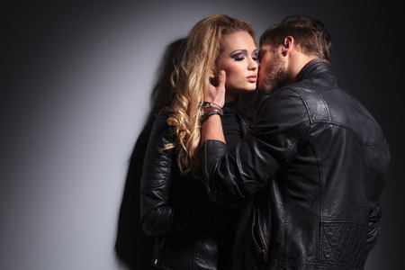 W miłości mody para pocałunek na szarym murze. Zdjęcie Seryjne