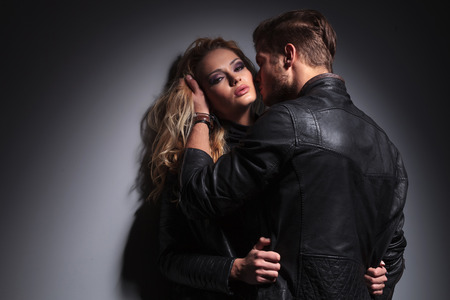 Blond fashion man holding his lover hair while trying to kiss her on the cheek, against a grey wall.