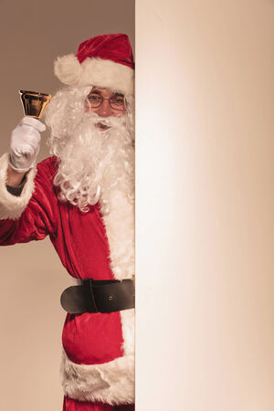 Santa Claus holding a golden bell in his hand while presenting a blank board. photo