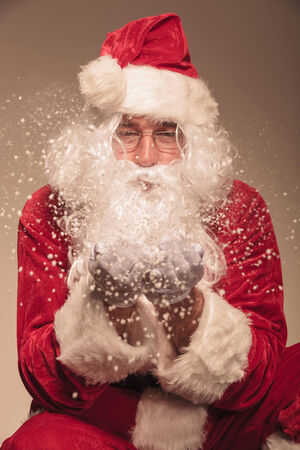 Close up picture of Santa Claus blowing snow to the camera. photo