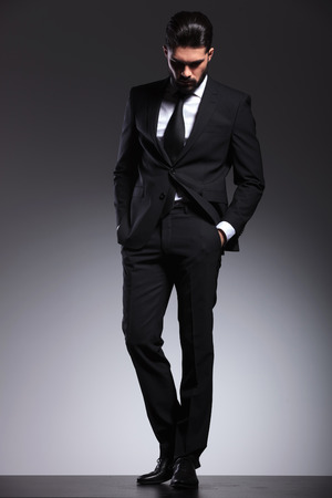 body image: Full body image of a young elegant business man looking down while holding his hands in pockets.