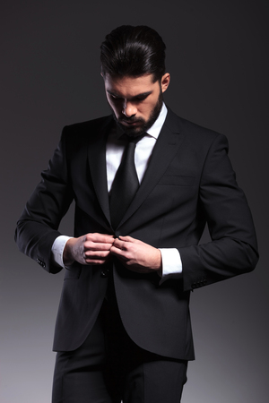 man looking down: Elegant business man closing his jacket while looking down, on grey background.