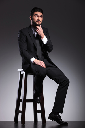 body image: Full body image of a young business man fixing his beard, thinking while sitting on a stool.