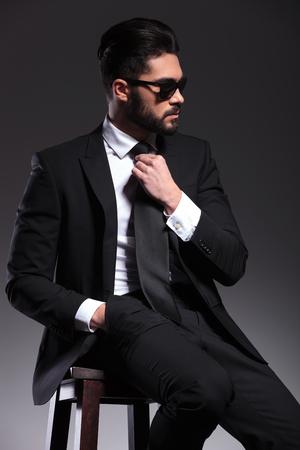 hombre sentado: Vista lateral de un hombre de negocios elegante que fija su lazo mientras mira lejos de la cámara.