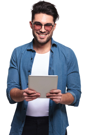 cool dude: Happy young casual man smiling for the camera while holding a computer tablet in his hands, isolated.