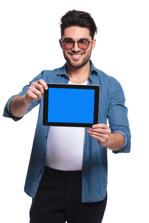 latin man: Young fashion man smiling for the camera while presenting a tablet computer, isolated. Stock Photo