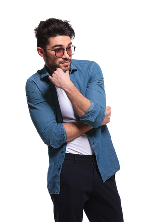 undershirt: Attractive young casual man looking away while holding his hand to his chin. Stock Photo